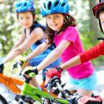 tri deti s prilbami na detskych bicykloch