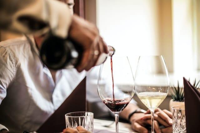 nalievanie cerveneho vina do pohare vedla bieleho vina
