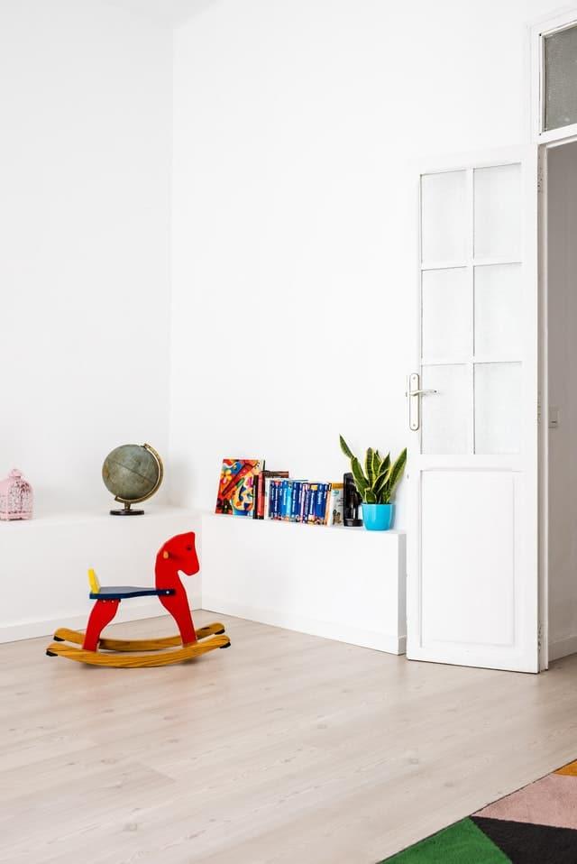 minimalismus_v_detskej_izbe_polica_knihy_globus_hojdaci_konik_biele_steny_dvere