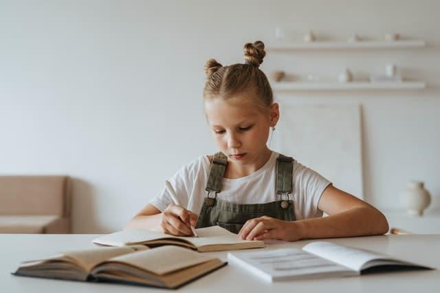 skolske-potreby-pre-dieta-dievcatko-za-stolom-riesi-domace-ulohy