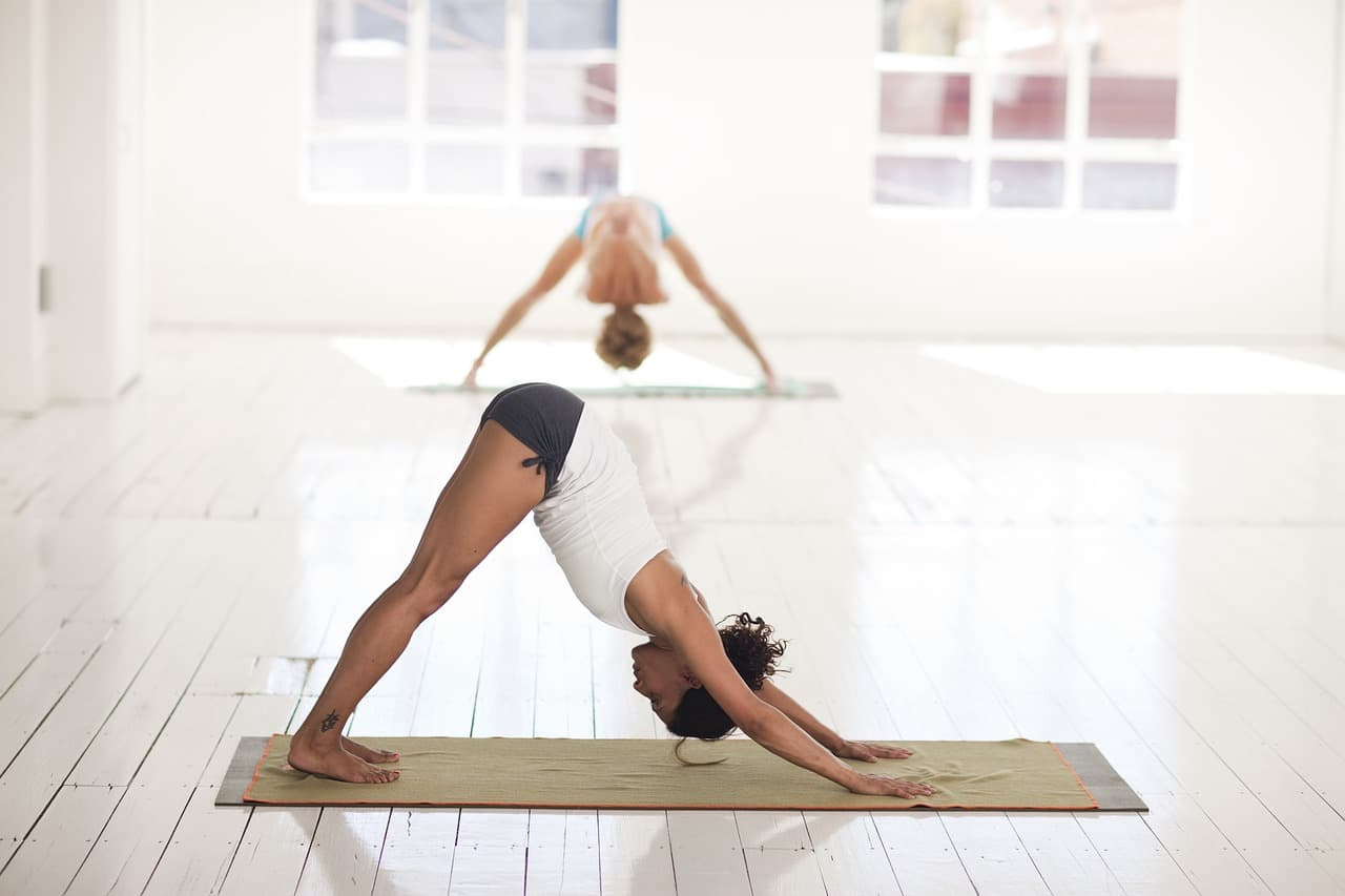 joga s dvoma zenami v pozicii pes hlavou dolu