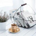 zlata salka caju na bielom stole vedla rastliny a kosika s knihami